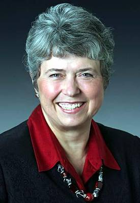 Headshot of Rep Sharon Cissna, wearing red shirt and suit jacket